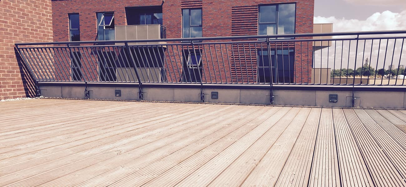 Timber decking used on a terrace with a black fence