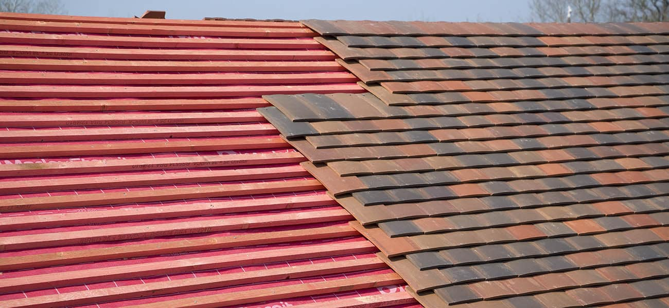 Work in progress on a roof with clay tiles