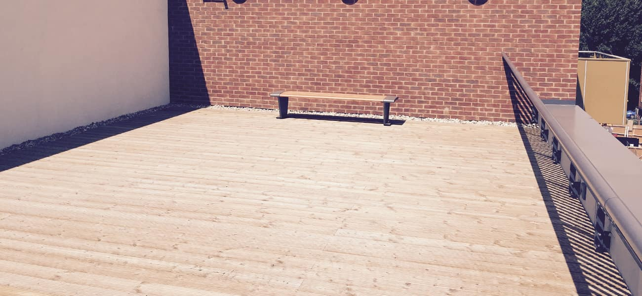 Timber decking terrace with a bench at the back