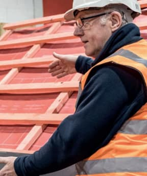 An image of a building site foreman, talking to builders next to a roof that is partially built.