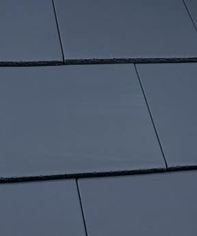 A close up image of black, Edgemere, smooth slate tiles in situ on a roof.