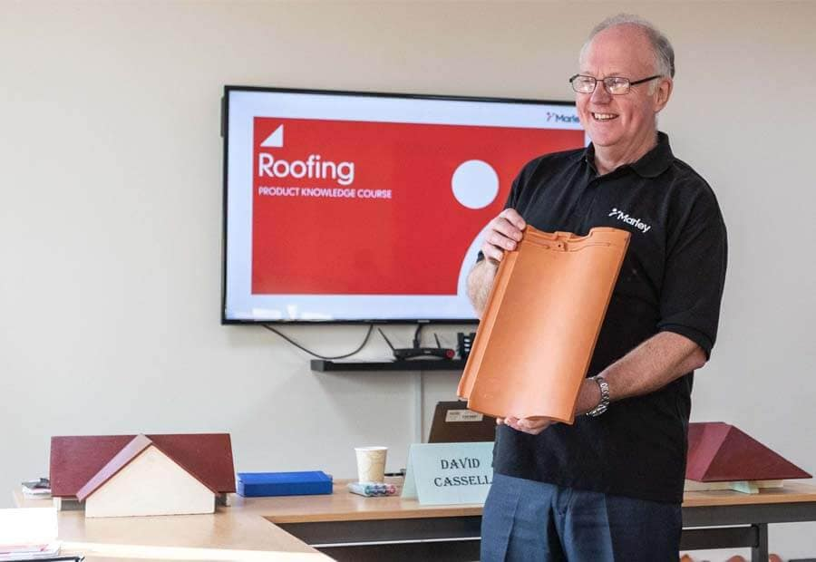 training manager holding a lincoln clay tile