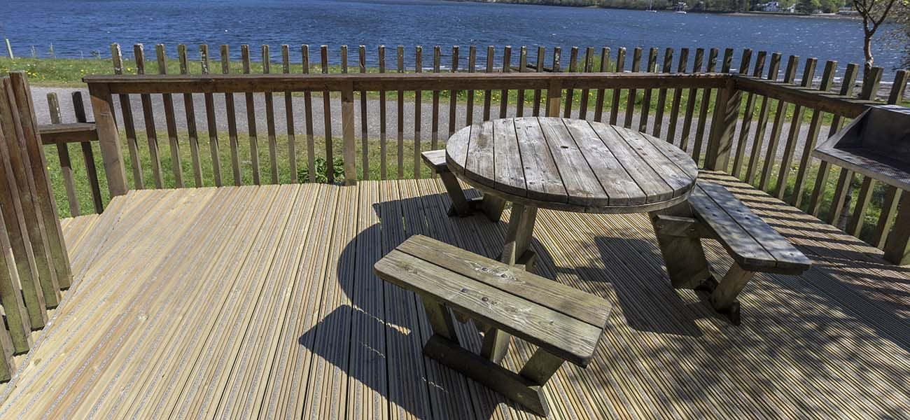 An image of anti-slip plus timber decking, from Marley, laid outside with outdoor furniture placed on top.