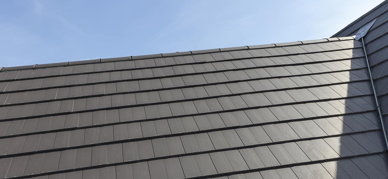 An image of a dark grey, slate tile, available from Marley slate roof specialists, in place on a roof.